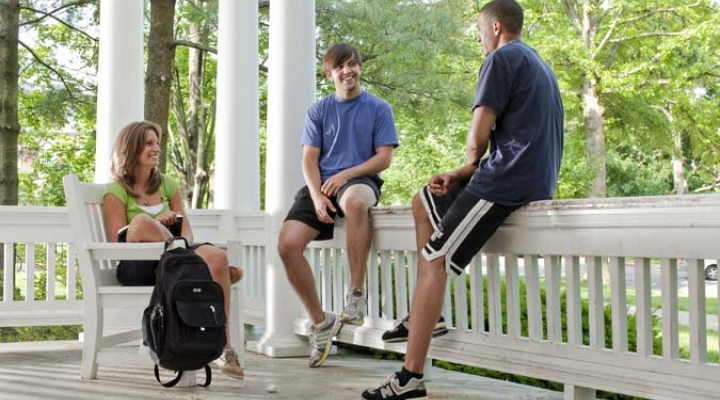 Three students talking on porch. Green trees behind them.